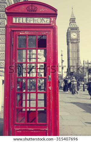traditional red phone booths in London with the Big Ben in a desaturated background, vintage - stock photo