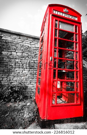 Traditional red telephone box booth or public payphone, village Bibury England UK