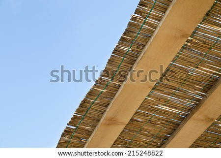 traditional reed and wooden roof with blue sky - stock photo