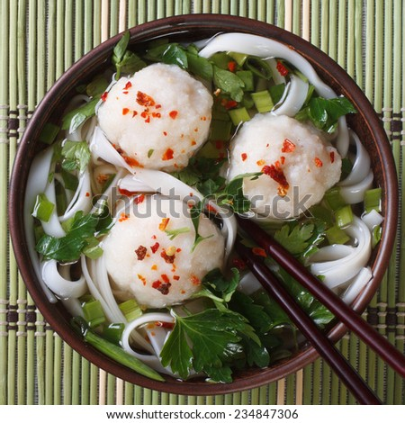 Traditional rice noodle soup with fish balls on a bamboo table closeup. top view  - stock photo