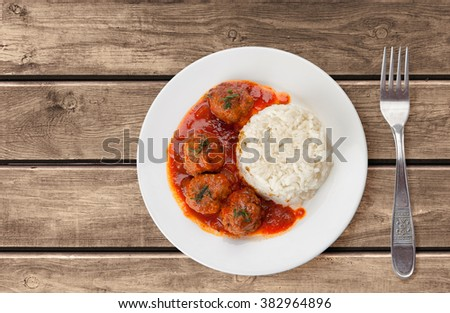 Traditional roasted meatballs with rice and tomato sauce - stock photo