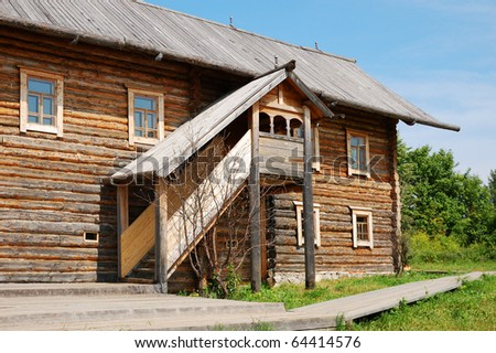 Traditional russian rural house at midday with green grass - stock photo