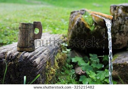 Traditional rustic wooden cup near clear water spring - stock photo