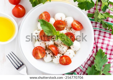 traditional salad with mozzarella and cherry tomatoes, top view, horizontal - stock photo
