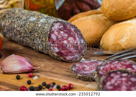 traditional salami with herbs on wooden board - stock photo
