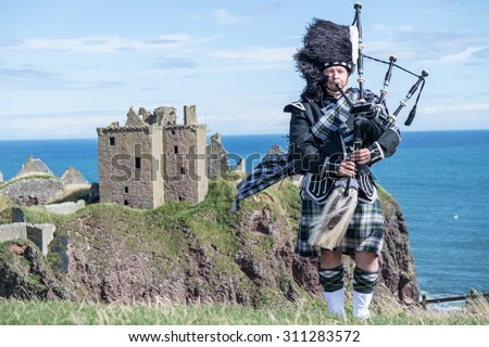 Traditional scottish bagpiper in full dress code at Dunnottar Castle in Stonehaven - stock photo