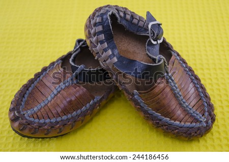 Traditional Serbian lether shoes on yellow - stock photo