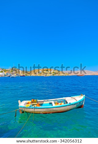 traditional small fishing boat docked in the main port of Symi island in Greece - stock photo