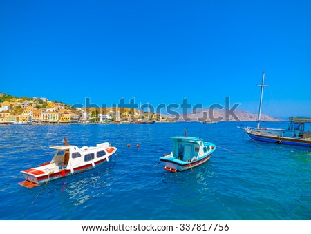 traditional small fishing boats docked in the main port of Symi island in Greece - stock photo