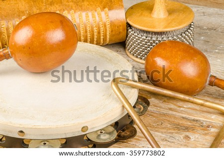 Traditional small percussion instruments in a still life on a rustic wooden surface - stock photo