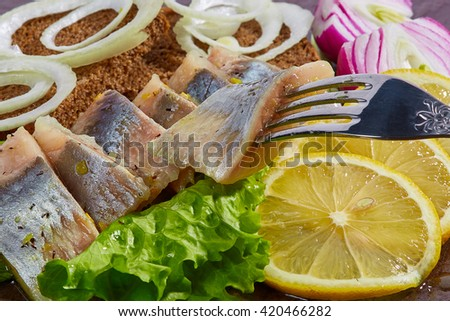 Traditional snacks Russia and northern people: salted herring with onion and lemon - stock photo