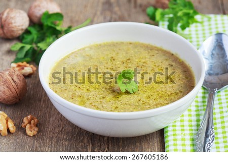 Traditional soup kharcho of beef broth with walnuts, cilantro and green tkemali on a wooden table. Selective focus. - stock photo