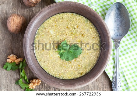 Traditional soup kharcho of beef broth with walnuts, cilantro and green tkemali on a wooden table, rustic style. Selective focus. - stock photo