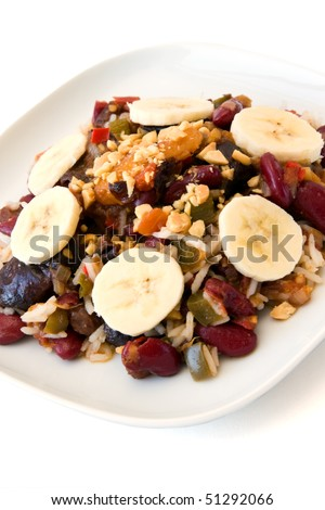 Traditional South African vegetarian curry made from kidney beans and dried fruits, served with rice, bananas and peanuts as cut out image. - stock photo