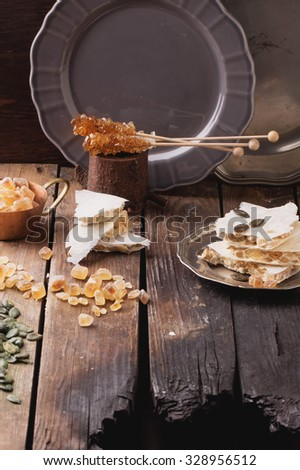 Traditional Spanish Christmas candy turron served on rustic wooden board with honey, pumpkin seeds and sugar candies. Dark rustic style - stock photo