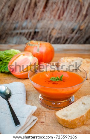 Traditional Spanish cold gazpacho soup in glass bowl with bread and ingredients on wooden table