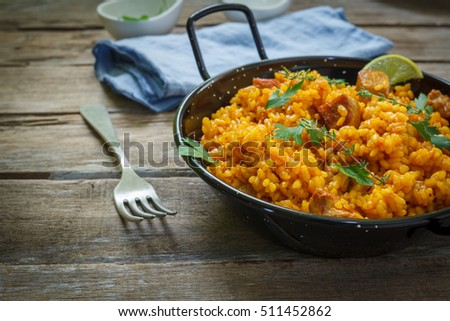 traditional spanish paella rice with chicken and meat on pan