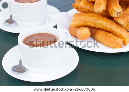 traditional spanish pastry - white cup of chocolate and pile of churros  - stock photo
