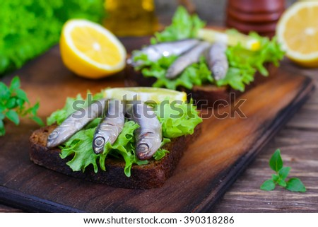 Traditional Spanish sandwiches with anchovies, lettuce and lemon on a wooden background - stock photo