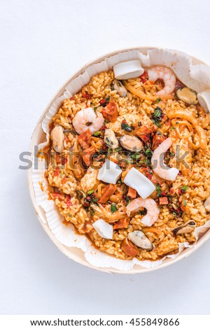 traditional spanish seafood paella, overhead on white cloth