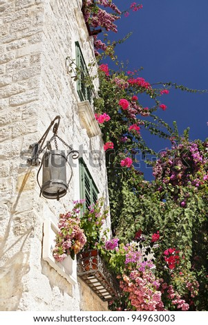 Traditional stone house with lantern and window, overgrown with red flowers in Croatia - stock photo