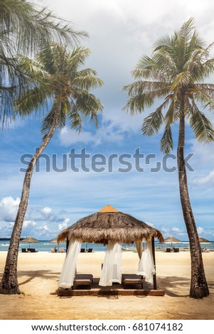 traditional straw parasol and palm tree in beautiful beach and cloudy sky