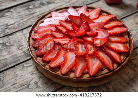 Traditional strawberry tart on vintage wooden background. Delicious summer pastry dessert food. - stock photo