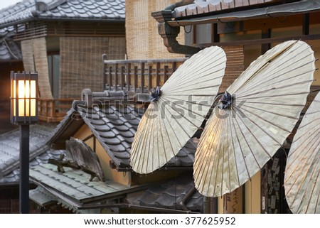 Traditional street scene detail at dusk after the rain, with lamp and shop umbrellas, in the old Sannen Zaka area of Kyoto, Japan - stock photo