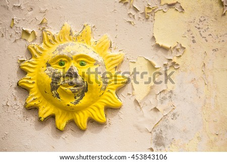 Traditional Sun Relief on Peeling Painted Wall