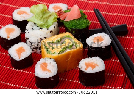 Traditional sushi and chopstick on a red bamboo napkin. Series japanese food - stock photo