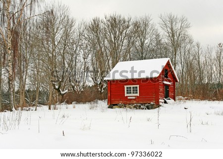 Traditional Swedish red wooden house covered by snow. Scandinavian winter.