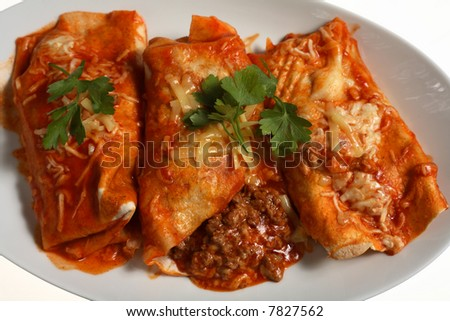 Traditional tex-Mex enchilladas, spicy ground (minced) beef wrapped in a corn tortillo and baked with a coating of tomato salsa and cheese. - stock photo