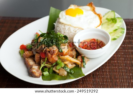 Traditional Thai dish crispy pork with a fried egg atop the jasmine rice served with chili sauce - stock photo