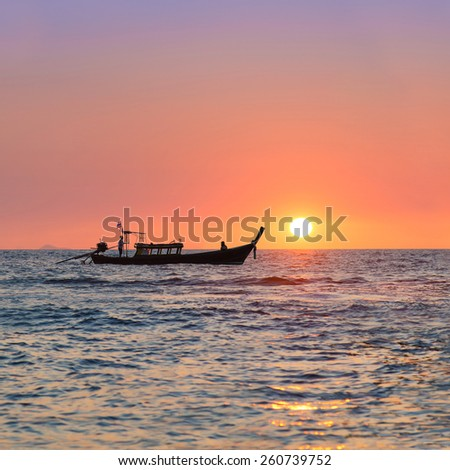 Traditional thai long tail boat against sunset above ocean, Thailand, Krabi province, Andaman sea - stock photo