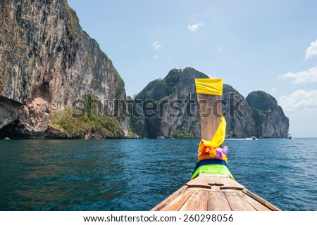 Traditional Thai Longtail boat and island of Phi Phi Leh on the horizon,Thailand - stock photo