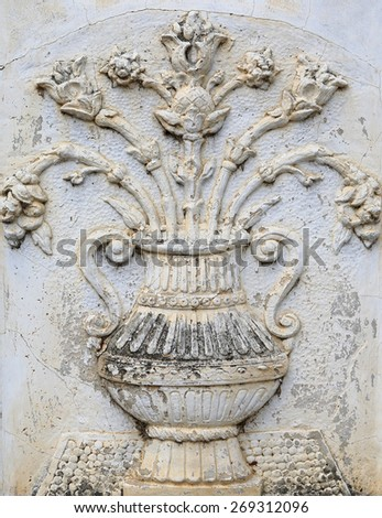 Traditional thai style carved of vase and flower on wall - stock photo