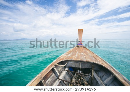 Traditional Thai wooden longtail boat heads out into the Andaman Sea on a day trip from Koh Phi Phi Island - stock photo