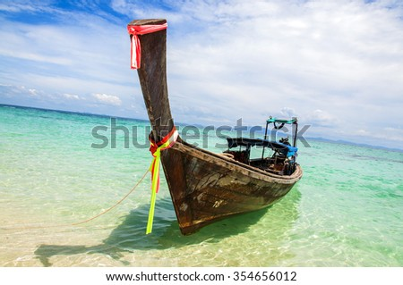 Traditional Thai wooden longtail boats with decorative sash ribbons moored in crystal waters on the shore of Bamboo Island near Krabi - stock photo