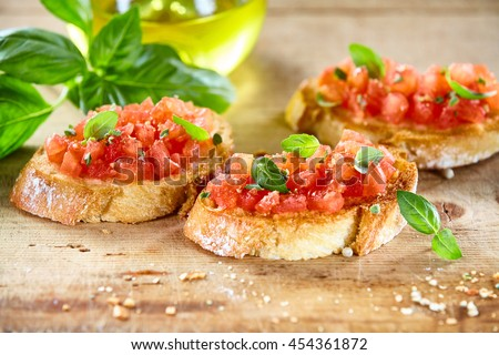 Traditional toasted Italian tomato bruschetta seasoned with spice and garnished with basil served on a rustic wooden board - stock photo