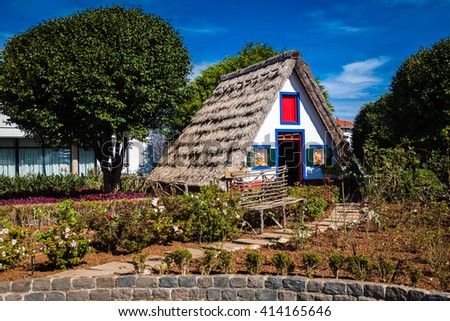 traditional triangular Madeira house, built of wood and thatched with straw - stock photo