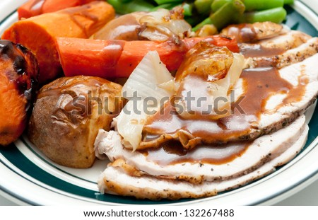 traditional turkey dinner with crispy skin, turkey slices and fresh roasted  vegetables smothered in gravy perfect for Christmas dinner and Thanksgiving meals