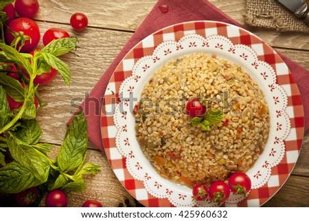 Traditional Turkish Ramadan iftar food Bulgur pilavi pilaff with tomatoes and rice concept background - stock photo