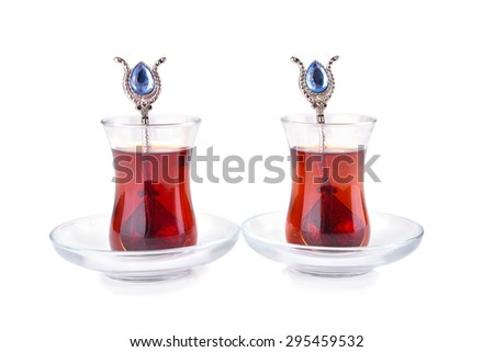 Traditional turkish tea in two glasses with spoons on white background