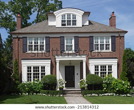 Traditional two story brick house with dormer window - stock photo