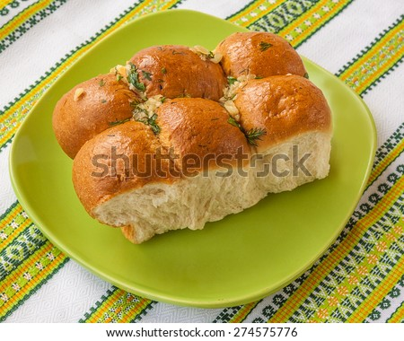 "Traditional Ukrainian borsch bun to ""pampushka"" with garlic on embroidered towel - stock photo"