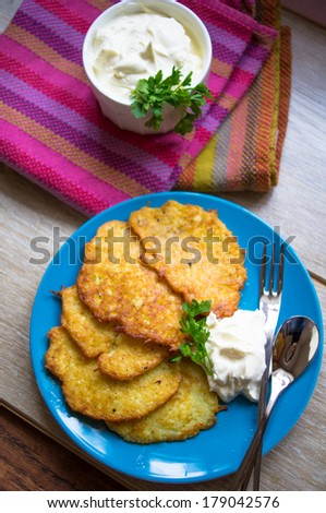 Traditional ukrainian dish - fried potato pancakes or deruny on the plate with sour cream