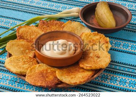 Traditional Ukrainian homemade potato pancakes potato, green spring onions with sour cream - stock photo