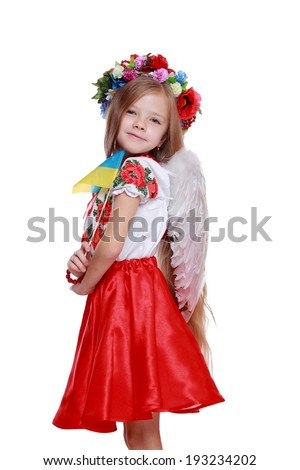 Traditional Ukrainian little girl  holding national flag from east Europe/Emotional little girl in a beautiful Ukrainian costume with white wings on Holiday theme