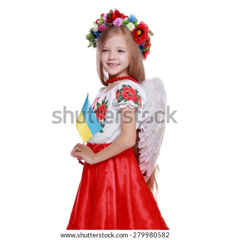 Traditional Ukrainian little girl  holding national flag from east Europe/Emotional little girl in a beautiful Ukrainian costume with white wings on Holiday theme - stock photo