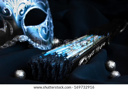 Traditional venetian carnival mask and a fan - stock photo